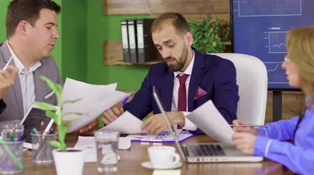 yönetim kurulu : Bearded team leader in business suit having a meeting with his investment team. Young leadership. Stok Video