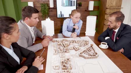 мини : Female architect explaning her real estate project to young investors in the conferenc room. Mini town.
