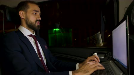 move well : Businessman in suit sitting on the back seat of his limousine working on laptop. Businessman typing on laptop in car. Stock Footage