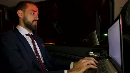 move well : Businessman in suit working late on his laptop on the back seat of his car with personal driver. Happy businessman. Stock Footage