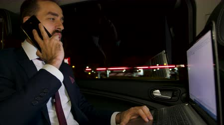 erişilebilirlik : Businessman yelling during a phone call sitting in the back seat of his limousine. Night city lights. Personal driver. Angry businessman.