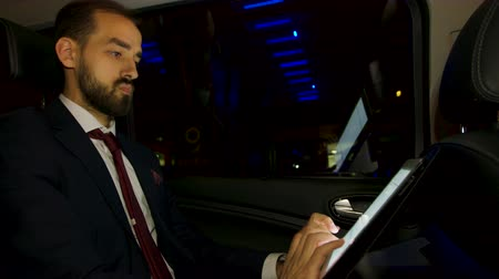 собственность : CEO thinking about his next business move in the back seat of his luxury car with personal driver. Businessman working on tablet. Night city lights. Стоковые видеозаписи