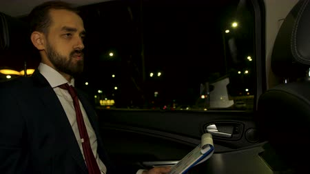 limuzína : Businessman at night in the back seat of his limousine signing documents on clioboard. Businessman with personal driver.
