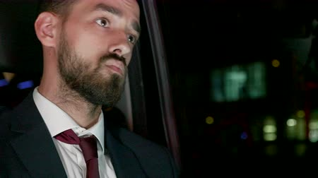 move well : Bearded businessman working on laptop from the back seat of his limousine stuck in traffic jam at late hours. Night city lights. Stock Footage