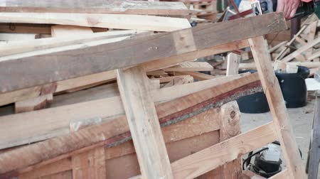 timber cutting : Man using an electric saw to cut wooden pallet in a ware house. Modern equipment tu cut wood.