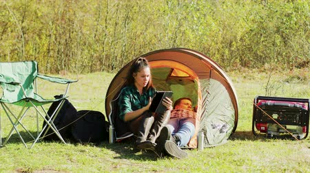 tentáculo : Beautiful young girlfriend using her tablet in front of camping tent while her boyfriends relaxing inside the tent. Stock Footage