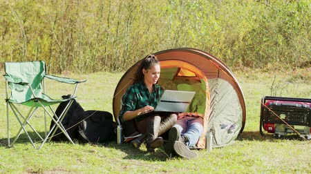 tentáculo : Beautiful young girlfriend laughing while working on her laptop in camping tent. Boyfriend relaxing while girlfriends working. Generator.