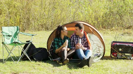 tentáculo : Beautiful couple having a conversation in camping tent in the wilderness and drinking hot drink. Camping essentials.