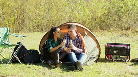 great story : Young boyfriend sharing a story with her girlfriend in front of their camping tent.