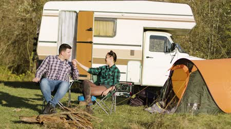 week end : Hipster boyfriend kissing his girlfriend hand while sitting on camping seats in front of their vintage camper van. Relaxing Week-end