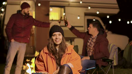 bulbo : Girl sitting on a camping chair in a cold night of autumn. Friends clinking beer bottles in the background.