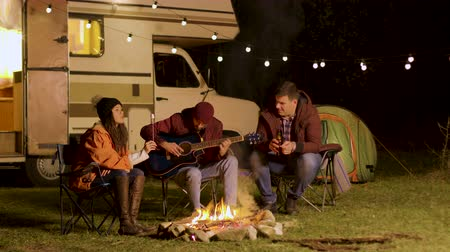 sharing : Man singing a song on guitar for his friends around camp fire in a cold night of autumn in the mountains. Retro camper van. Light bulbs.