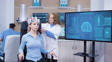 consciência : Neurology female doctor making adjustments to brainwaves headset of a pacient in modern braind laboratory. Assistant working in the background