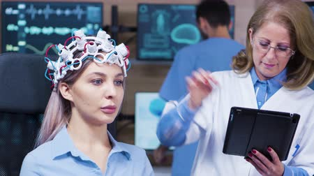 consciência : Female doctor in neuroscience using a futuristic device to read brain activity from her patient. Eeg.