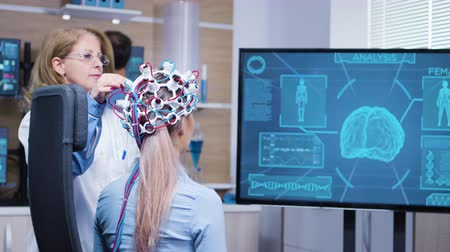 ученый : Female patient looking at her brain activity on tv screen wearing a headset to read her brain data.