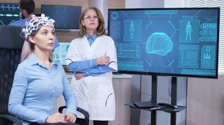 coscienza : Focused female neuroscientist making hand gestures in modern facility for brain study. Female patient with brainwaves scanning headest.