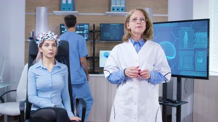 средства : Focused female neuroscientist making rotation hand gesture in laboratory for brain research. Female patient with brainwaves scanning headest.