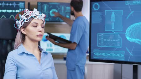 coscienza : Brain activity on tv screen from female patient with brainwaves scanning headest sitting on a chair. Model clinic for brain research.