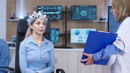 consciência : Neurology doctor holding clipboard in front of female patient brainwave scanning headset. Patient reading brain data.