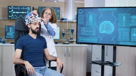 coscienza : Female scientis in research for brain activity adjusting brainwaves headset on male patient.