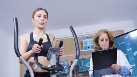 ekg : Female runner testing her cardio in a professional testing centre. Modern facility for athletes. Wideo