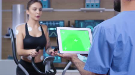 csatolt : Doctor holding tablet with green screen in front of athlete. Female athlete running with electrodes attached to her body.