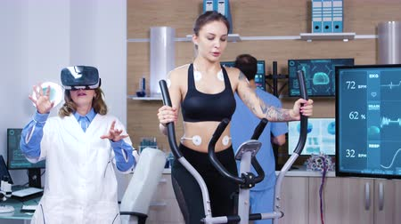 csatolt : Female doctor in sport scienese wearing virtual reality goggles while female athlete running with electrodes attached to her body. Stock mozgókép