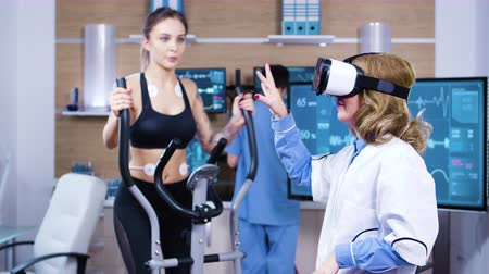 ekg : Female scientist with virtual reality goggles for sport measuring. Female athelete running with electrodes attached to her body.