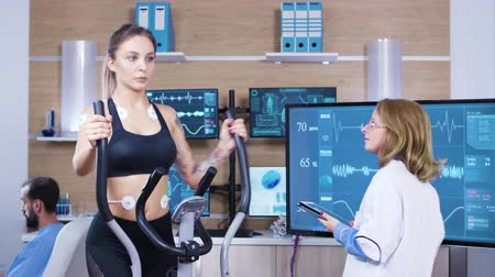 heart monitor : Female doctor in sport science testing woman athlete endurance in fitness centre. Female athlete running with electrodes attached to her body. Stock Footage