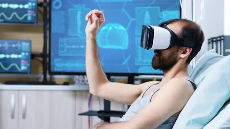 カラット : Patient with virtual reality goggles in a modern facility for brain research making hand gestures sitting on bed.