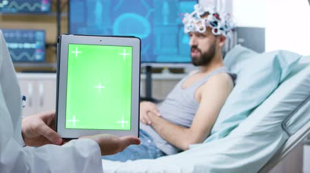 coscienza : Doctor in a neurology clinic holding digital tablet with green screen. Patient wearing brainwaves scanning headset.
