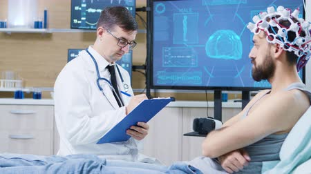 coscienza : Doctor in brain research staying next to patient bed and taking notes on clipboard. Patient wearing brainwaves scanning headset.