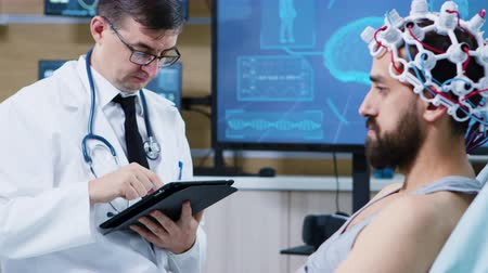 coscienza : Patient sitting on hospital bed and wearing brainwaves scanning headset. Doctor using tablet.