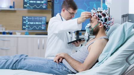 coscienza : Doctor holding tablet and making adjustments on brain sensors attrached to patient. Patient wearing brainwaves scanning headset and air mask.