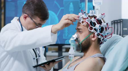 coscienza : Doctor in a modern facility for brain research looking at tablet and making adjustments on brainwaves scanning headset of his patient.