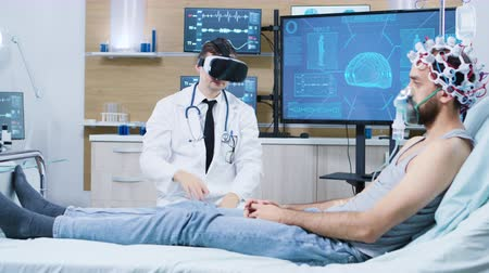 csatolt : Doctor wearing virtual reality goggles in a modern facility for brain analysis. Patient sitting on bed with brain sensors attached and air maks