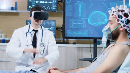 consciência : Doctor in a neuroscience centre wearing a virtual reality goggles Patient sleeping on a hospital bed wearing brainwav scanning headset and air mask.
