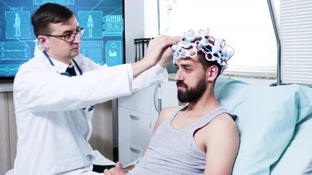 consciência : Doctor in a neuroscience centre preparing patient for brain analysis. Patient wearing brainwaves scanning centre.