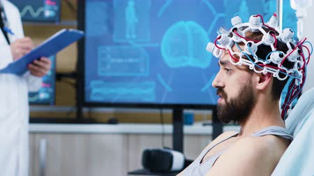 consciência : Patient with brainwaves scanning headset sitting on bed in modern facility for brain research. Doctor taking notes on clipbard