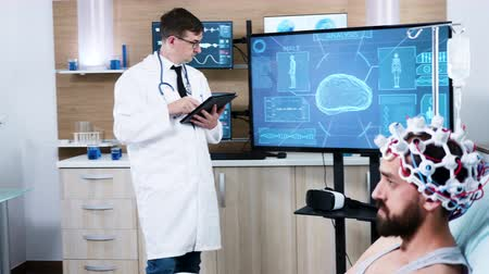сканер : Doctor in neuroscience centre using modern technology. Patient wearing brainwaves scanning headset.