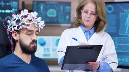 doença : Female doctor taking notes while patient is wearing brains sensors. Medical centre for brain research.