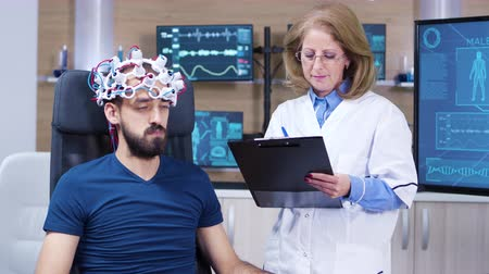 consciência : Female neurologist writing diagnose for male patient while wearing brainwaves scanning headset.