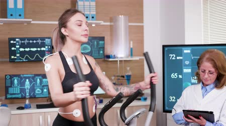 heart rate : Beautiful female athlete running in modern facility for sports science. Female athelete in sportwear running with electrodes attached to her body. Stock Footage