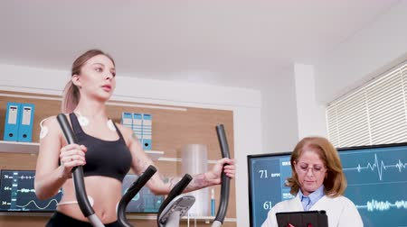 ekg : Beautiful female athlete using hi-tech technology to increase her performance. Female athlete running with electrodes attached to her boyd. Wideo