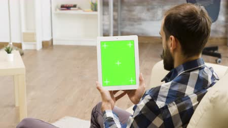 вертикально : Man holding vertically a digital tablet PC with green screen in a modern and bright living room