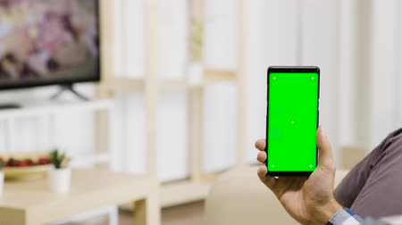 vertically : Holding vertically a green screen phone in hands in modern and well lit living room. Parallax dolly shot Stock Footage