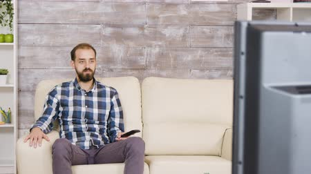 changing channel : Bearded man sitting with serious face watching tv and holding remote control. Zoom in effect Stock Footage