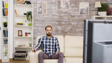 changing channel : Bearded bored man watching television sitting on couch. Man holding tv remote control. Stock Footage