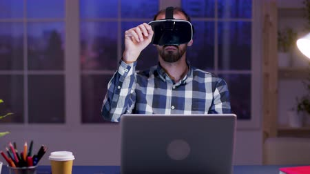 késő : Young businessman using virtual reality goggles while working in home office during at night.