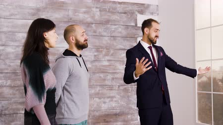 fizetés : Real estate agent in suit presenting new apartment to beautiful young couple.